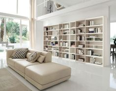 Book Display with Couch is giving a User a Space to get Relax & Read. The whole Space has a Combination of White & Beige. Glass Façade is Visually Connecting the Indoor with the Outdoor & Allowing Natural ✨ Light Inside - GharPedia Living Room Wall Units, Bookshelves In Living Room, Living Room Cabinets, Living Room Storage, Living Room Modern, Wall Storage, Modular Bookshelves, Wall Unit Designs, Bookshelf Design