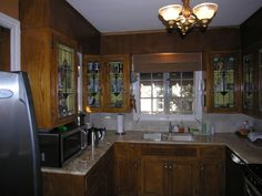 1923 bungalow kitchen. Lovely leaded glass panels in doors. Too bad these owners ripped out the cabinets to put in a wholly unremarkable kitchen.