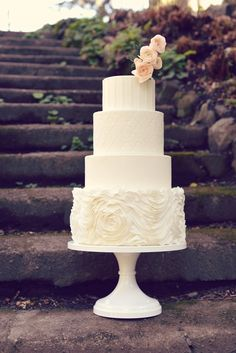 Four tiered elegant white modern wedding cake with subtle white stripes, Moroccan tile, and rosette ruffles, topped with coral sugar flowers. Wedding Cake Boards, Wedding Cakes, Wedding Venues, Wedding Ideas, Sugar Flowers, Silk Flowers, Unique Cakes, Cake Shop, Custom Cakes