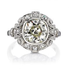2.69ct M/VS1 EGL certified vintage Cushion cut diamond set in a handcrafted platinum mounting. An Art Deco design featuring a bezel set diamond and beautiful scroll work.