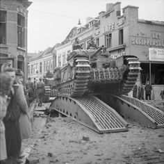 Churchill tanks of 34th Tank Brigade cross a temporary bridge in Roosendaal, 30 October 1944.