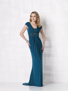 IN STOCK, in peacock. Sleeveless matte jersey A-line dress with ruched portrait collar, V-neckline with detachable hand-beaded modesty piece, beaded Empire waistband, center gathered skirt with sweep train. Matching shawl included. Sizes:4 – 20, 16W – 26W