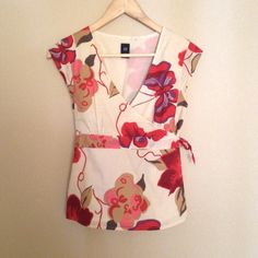 GAP short sleeve wrap top Gorgeous wrap top in a bold floral print by GAP. Light weight cotton with accentuated tie waist and cap sleeves. Easily dressed up or down. Chic addition to any outfit. Worn only a few times and excellent condition. GAP Tops Blouses