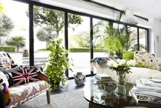 A wall of windows opens onto the garden and outdoor living spaces beyond.