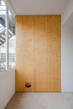 Decoração de apartamento pequeno, decoração minimal, paredes brancas, porta de madeira.