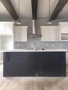 East Nashville classic modern craftsman kitchen. Wood beams, marble backsplash, white cabinets with black shiplap island. Superior Development LLC.