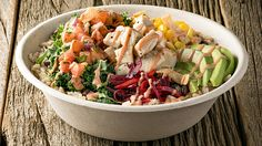 Freshii's Oaxaca Bowl, a base of brown rice and kale topped with avocado, beet slaw, black beans, corn, crispy wontons, salsa fresca, spicy yogurt dressing and a lime wedge and optional choice of protein