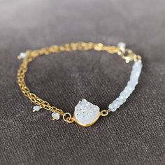 This opalescent druzy, diamond and moonstone bracelet is part of the Artique Boutique Bridal collection. Its perfect for wedding jewellery, whether that be as a bridal bracelet, a bridesmaid bracelet, a wedding gift, or if you are simply attending as a wedding guest. Alternatively, this delicate bracelet can be worn everyday for a touch of luxury and elegance. The centrepiece is a teardrop shaped druzy stone with an iridescent finish - the colours are beautiful and mesmerising - they remind…