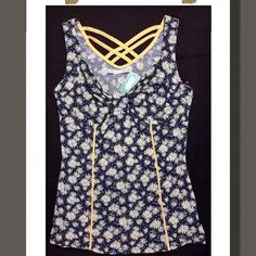 Top Maurice's Daisy tank top with a criss cross back..a really cute top!  96%Polyester  4% Spandex Maurices Tops Tank Tops