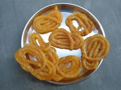 Pour oil in pan and heat it.  Now, after getting oil hot, take Jalebi batter into cloth and make a small hole at the end of the cloth.  Now, press the cloth so that the jalebi batter comes out of the hole we made at one end of the cloth and drops into hot oil in circular shapes (pretzel shape).