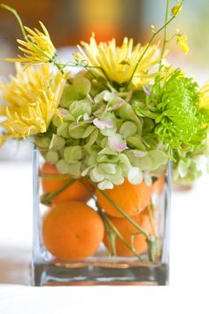 Fruit and flowers centerpiece with whole oranges, green hydrangea, green and yellow spider mum, curly willow tips. Hint: using whole fruit gives a great look while keeping your water clean and clear. Design by pamm meyers & Bridal Blooms & Creations.
