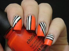 Bright orange nails with black and white stripes