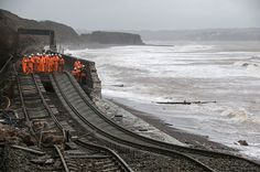Credit: Matt Cardy/Getty Railway workers inspect the main Exeter to Plymouth  railway line that has been closed due to parts of it being was...