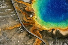 Yellowstone's Grand Prismatic Spring, Wyoming, USA The Grand Prismatic Spring is one of Yellowstone's most popular attractions. The color is caused by bacteria that grow around the edge of the hot spring.