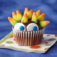 Peeking Monster Cupcake  This frightful cupcake is sure to be a monster hit at your Halloween get-together. Big eyes and spiky hair transform a plain cupcake into a special Hallow's Eve treat.  To make the cupcake, follow these steps:  1.	Insert sour candy corn in the frosting for hair.  2.	Cut one thin candy wafer in half and place at the top of baking cup for eyes.  3.	Use frosting to stick two blue mini candy-coated chocolates to thin candy wafer for pupils.