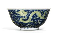 An underglaze blue and yellow enamel 'dragon' bowl Kangxi mark and period, the rounded sides rising from a straight foot to a gently flared rim, painted to the exterior in yellow enamels with two dragons pacing amongst flame wisps and clouds in pursuit of flaming pearls, all reserved on an underglaze-blue wave ground, the interior similarly decorated, the base inscribed with a six-character reign mark within a double-circle 13.8cm., 5 1/2 in.