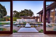 Step out the door into the peaceful Asian-inspired garden of this modern home. Concrete slabs create walkways and a bridge across the rectangular pond. Gravel beds and ornamental grasses keep the landscaping low maintenance.