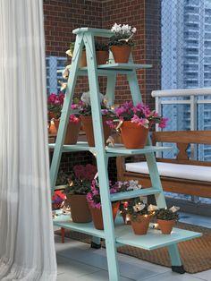 Pintada do mesmo tom da árvore, a escada de madeira (Escadas Hillos) acomoda prateleiras (Peg Faça) para receber os vasos de cerâmica (Jardineiro Fiel), adornados por asas de feltro (Paola Abiko) com luzinhas.