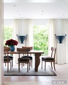 """The dining table and chairs are by [ Jean-Michel] Frank, and the 1930s rug is Swedish; custom-made pedestals of French limestone support Swedish cast-iron urns from the '20s. Oak dining table surrounded by klismos chairs."" Design by Carlos Aparicio. Styled by Stephen Pappas. Photography by Richard Powers. ""Miami International: Carlos Aparicio's Florida Home"" by Susan Zevon. Elle Decor."