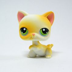 Littlest Pet Shop # 73 kitty is among the earliest pets and comes the rare Curious Kitties play set that had 3 playful kittens. This kitty is white with shades of yellow that fall just short of orange. Pink inner ears and blues eyes,raised paw. Excellent condition, displayed only and never played.