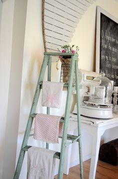A vintage ladder for a towel rack in the kitchen...cute!