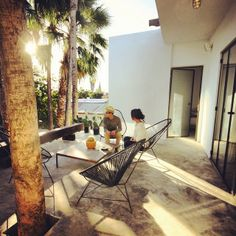 DRIFT SAN JOSE in Baja Mexico. Acapulco Chairs, Patio, Palms, Steel doors Drift San José - Artisanal Mezcal Bar, Food Cart Events, Design Shop, Industrial Boutique Hotel Style, Adventure and Culture Travel, Located in San José del Cabo, Los Cabos, Baja California Sur, Mexico.