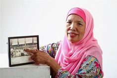 Fond memories: Mak Cik Salmiah pointing at an old photo of her in a group shot…