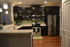 mint green/ aqua kitchen with pendant lighting, glass subway tile backsplash