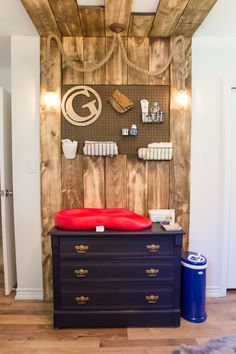 This is one heck of a baby changing table accent wall. Wooden slates and peg board make for a rustic look while keeping mama organized.
