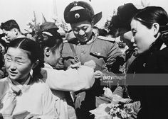 Korean girls present a member of the Chinese People's Volunteer Army with a bouquet of flowers prior to the mass withdrawal of Chinese troops from North Korea.