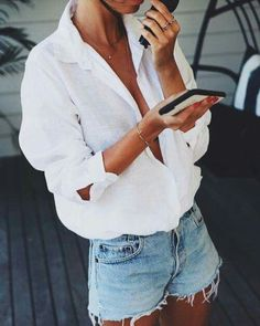 White shirt paired with ripped denim shorts