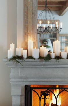 white candles and greenery on the mantel