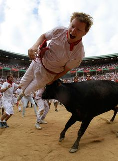 A wild cow tosses a reveler following the second day of the Running of the Bulls at the bullring during the San Fermin festival in Pamplona on July 8. (Joseba Etxaburu/Reuters)