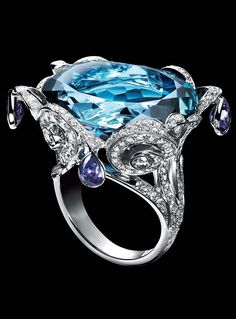 Piaget Limelight embroidery motif ring in 18K white gold, set with one brilliant-cut blue topaz (approx. 36 ct), 4 pear-cut purple sapphires (approx. 2.5 ct) and 273 brilliant-cut diamonds (approx. 2.8 ct).