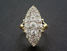 A spectacular Victorian diamond ring! This is a navette- shape ring; a popular style that is seen throughout the late Georgian and Victorian eras. The ring is pave-set with old mine-cut diamonds of varying size and shape to give a superb display of sparkle and brilliance. The ring is made from 18ct gold with carved setting detail and split, decorative shoulders. A fabulous antique engagement ring!  Gemstones: - The ring has twenty-seven old mine-cut diamonds in various sizes and shapes. We…