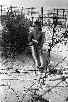 Woman sitting and reading on the beach surrounded by barbed wire, Bournemouth, 1944