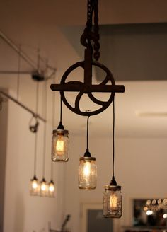Old Lighting...lights in old mason jars...strung on an old rusty pulley.