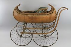 VICTORIAN CANOE FIGURAL BABY'S CARRIAGE  Very rare example, reed and wood slat, shaped with ornate finials, canoe design body, large spoke wheels, a truly luxury early pram, with all wood handles, plush interior done in blue upholstery.