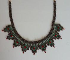 Renkli kum boncuklarla etnik bir tarzda tasarlanmış kolyenin ortalarında kristal boncuklar bulunmaktadır. Uzatma zinciri sayesinde her boyun için uygun boyuta ayarlanabilir.Lacivert-beyaz-mavi kristal, krem-yeşil-kırmızı kristal, köy boncuğu-yeşil-kırmızı kristal, siyah-kırmızı-yeşil kristal ve siyah-metalik gri-parlak kristal boncuklar kullanılarak yapılmış modelleri mevcuttur.
