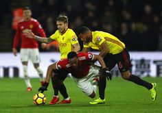Anthony Martial of Manchester United is challenged by Kiko Femenia and Adrian Mariappa of Watford during the Premier League match between Watford and...