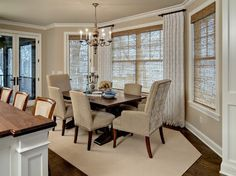 """These stationary silk panels are hung between each window with a """"short"""" rod creating a softened effect in this dining space."""