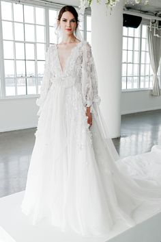 A-line wedding dress with deep V-neckline, long sleeves, watteau train, bow, and 3D floral appliqués