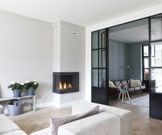 Modern living room idea with dark glazed sliding doors and corner fireplace House, Home, Home Fireplace, House Styles, New Homes, House Interior, Home Deco, Home Interior Design, Home And Living