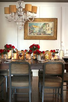 Dining room tablescape with red roses  - Via: Design*Sponge - Tell me that the one crooked chandelier shade doesn't bother anyone else!??!