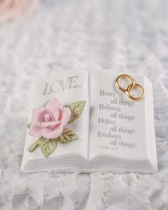 This delicate fine porcelain bible showcases a lovely pink rose in bloom and a pair of entwined wedding rings accented with 24K gold. The inscription from 1 Cor. 13.7 reads: <br />Love... <br />Bears all things <br />Believes all things <br />Hopes all things <br />Endures all things.