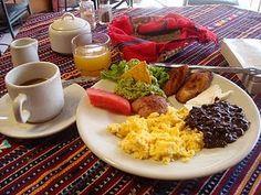 Desayuno guatemalteco con Huevos revueltos, plátanos fritos, frijoles negros, queso, guacamol y fruta