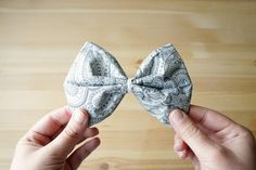 """Try """"the bow"""" napkin fold. 1)With the napkin face down, fold the top edge and bottom edge into the middle  2)Repeat! (fold the top and bottom edges to the middle again - will look like a skinny rectangle)  3)Fold left edge into the middle; fold the right edge into the middle overlapping on top of the left (should look like a neatly folded square now)  4)Turn the napkin over and cinch the middle with string, twist ties, ribbon. Fluff and pull as needed to get the desired bow shape."""