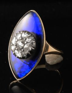 Gold, blue crystal and diamond ring. 18th century The oval bezel is centering an important cluster of diamond set in silver on a lapis blue convex crystal ground.  These rings were ceremonial rings in use at the court.  French, late 18th century.