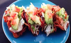 A bacon taco shell stuffed with shredded chicken, lettuce, avocado and tomato