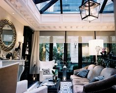 Living Room Photo - A glass ceiling and a black lantern in a living space with white wingback chairs